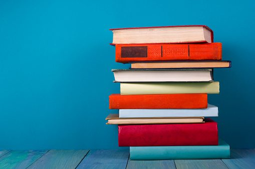 Image of stack of colorful books, grungy blue background, free copy space
