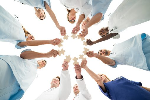 Image of Medical Team Joining Jigsaw Pieces In Huddle