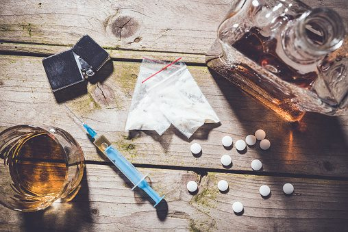 Image of drugs and alcohol displayed on a wooden table