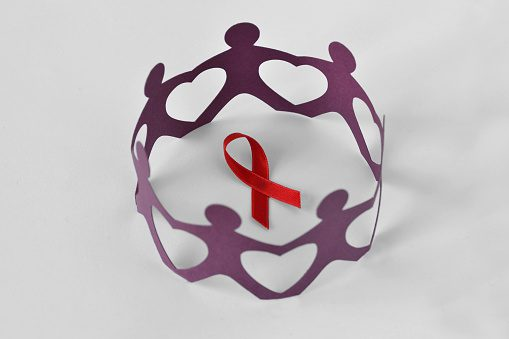 Paper people in a circle around red ribbon on white background - Aids awareness concept